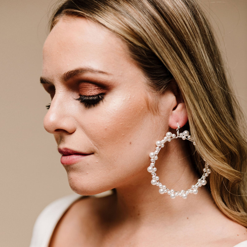 For a pretty, feminine bridal look, style your wedding dress with Siren Pearl Hoop Earrings ARE 611 by Arianna Tiaras at Limelight Occasions bridal boutique near Huddersfield, Wakefield and Leeds